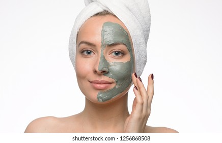 Emotional portrait of a happy and satisfied naked young woman with a blue clay cosmetic mask looking at the face with a smile forward during procedures in a beauty salon isolated on white background