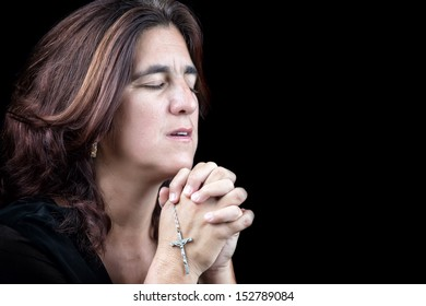 Emotional portrait of an hispanic woman praying with a small crucifix (isolated on black)