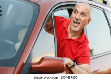 Emotional portrait of an impulsive and indignant mature European male with a bald head screaming to the driver leaning out of his car window during a traffic jam.Man in summer vacation.Summertime
