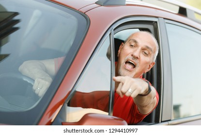 Emotional portrait of an impulsive and indignant tanned European mature man with a bald head,gesturing and screaming to the driver in a traffic jam sticking out of his car window.Summer city.Lifestyle