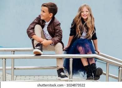 emotional portrait of laughing children. Children, a boy and a girl are sitting on the railing in the park friends. Concept of friendship. Brown and black leather jackets, blue skirt, long hair.
