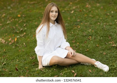 Emotional portrait of a naive and calm beautiful teenager girl looking at the camera while sitting on the grass in the park during a walk in the city. Girl in summer city. Summertime. Lifestyle