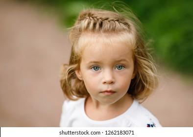 Emotional portrait of a pensive and beautiful little girl with blond hair, looking with interest at the lens on a walk in the park. Lifestyle. Childhood. Summertime. Summer vacation. Positive energy