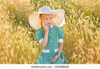 Emotional portrait of a pensive and beautiful little girl with blond hair and wearing a straw hat, looking away, sitting in a wheat field. Summertime. Summer vacation. Happy childhood. Positive energy