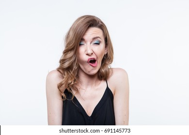 Emotional portrait. People. Body language. Young beautiful isolated white background. The face twitches. Sneezes. Disgustingly. A strange emotion. Awkward moment. Caught unawares