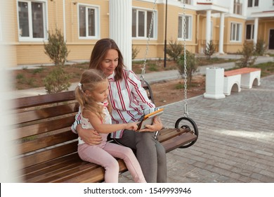 Emotional portrait of a positive and cheerful little girl with curly hair, looking at her mother. Happy childhood. Mom and daughter are studying on the tablet.
