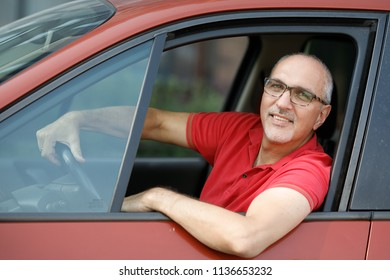 Emotional portrait of a positive and happy mature Hispanic man wearing glasses and a red T-shirt, with a smile on his face staring into the camera peeking out of the window of his car. Senior driver.