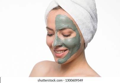 Emotional portrait of a positive and kind beautiful woman with a blue clay cosmetic mask on her face looking down with a smile isolated on white background. Lifestyle. Beauty concept. Lifestyle
