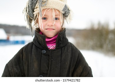 Emotional portrait of positive slavonic girl wearing loose fit padded jacket with scarf on her head in winter snowy day in village