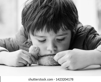 Emotional portrait of Sad boy putting his chin on teddy bear sitting next to window,Lonely kid with sad face,Child playing with brown bear and looking down with bored face in black and white photo,