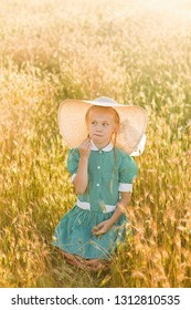 Emotional portrait of a surprised and funny little blonde girl with pigtails and a hat looking biting a blade of grass at her mother sitting in a field of wheat lit by the rays of the setting sun.