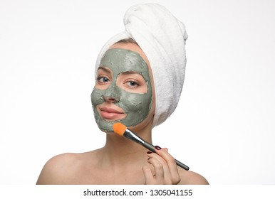 Emotional portrait of a tender and happy beautiful naked girl with a blue clay cosmetic mask on her face, looking into a mirror and applying clay with a brush, isolated on a white background. Beauty