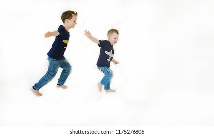Emotional portrait of two happy and mischievous little brothers playing and running after each other and isolated on white background. Lifestyle. Happy childhood. Positive emotions and energy