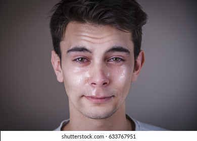 Emotional portrait of a young man crying and shedding tears