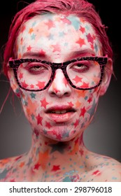Emotional portrait of a young sensual woman with stars on the face and painted hair in pink   wearing glasses