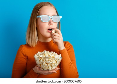 Emotional portrait of young woman in cinema glasses watching 3d movie. Keen focused teenager girl movie viewer in glasses eats popcorn with copy space isolated over blue color background.