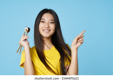 Emotional pretty girl with Asian appearance sushi rolls and chopsticks