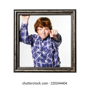 Emotional red-haired boy posing with picture frame isolated on white