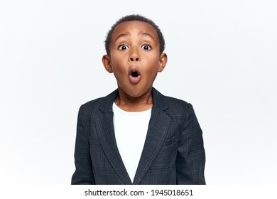 Emotional scared black little boy gasping and raising eyebrows seeing something scary. Emotional African child expressing shock, astonishment or fear, being speechless because of stupefaction