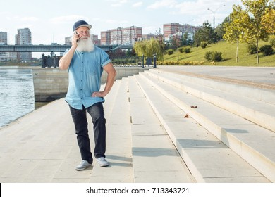 emotional senior man talking on the phone and laughing outdoor