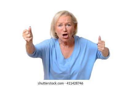 Emotional single senior woman dressed in blue blouse with angry expression and clenched fists over white background