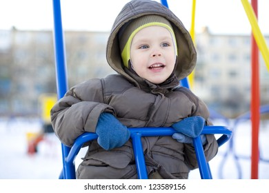 The emotional small child riding on a swing in winter