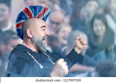 Emotional sport supporter with Iroquois haircut in colors of United Kingdom flag during a soccer or football match at the stadium