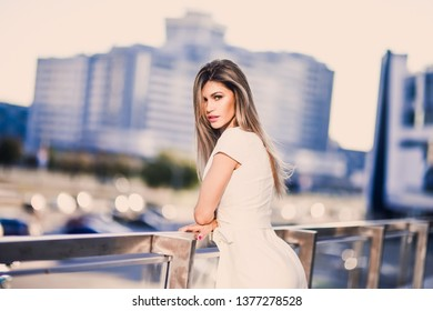 emotional spring summer portrait of Fashion stylish sexy of  young hipster blonde woman, elegant lady, bright colors dress, cool  girl. City view  urban lifestyle background.