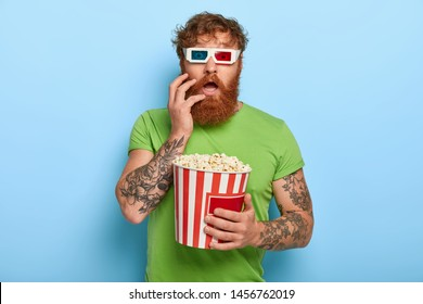 Emotional stupefied red haired man stares at camera through 3d cinema glasses, wears casual green t shirt, holds bucket of fresh popcorn, isolated on blue background. Shocked spectator indoor