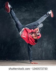 Emotional stylish dressed man performing break dance moves on the floor. Studio photo against a dark textured wall