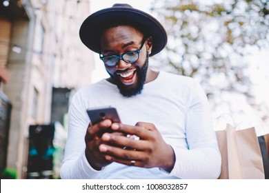 Emotional surprised african american guy with low prices in web store receiving message with promo code,excited dark skinned hipster guy in trendy hat overjoyed with winning online contest on web site