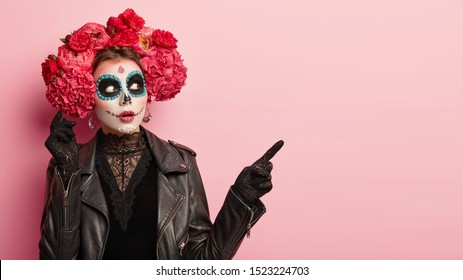 Emotional surprised woman wears face art mask, points away with fore finger, dressed in lace black clothes, red peonies wreath, demonstrates something for halloween. Dead bride with skull makeup