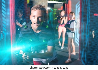 Emotional teen boy with laser pistol playing laser tag with friends on dark labyrinth