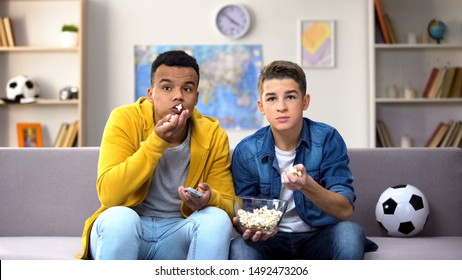 Emotional teen friends eating pop corn, cheering for favourite football teem