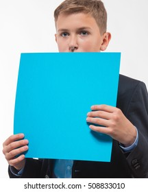 Emotional teenager boy blond in a blue suit with a blue sheet of paper for notes on a white background