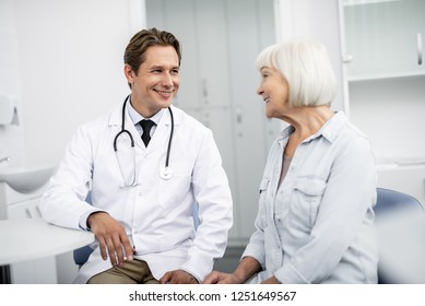 Emotional thankful aged woman sitting next to her professional general practitioner and smiling