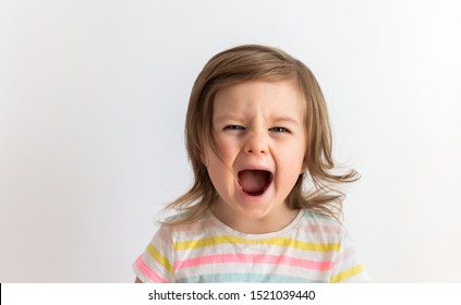 Emotional toddler child girl crying or screaming with mouth open, surprised happy baby portrait against white background