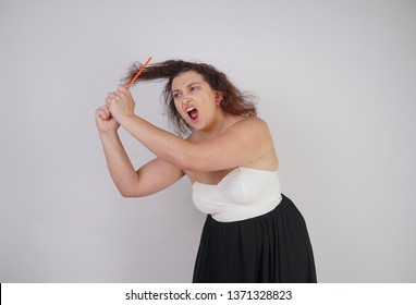 emotional unhappy woman with disheveled hair tries to comb them and suffers. curvy girl stands on white background in Studio alone.