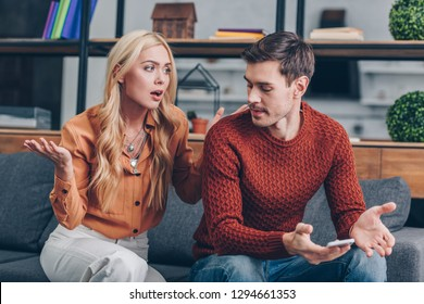 emotional upset couple sitting on couch and quarreling about smartphone, mistrust concept