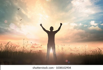 Emotional wellness concept: Silhouette of man raised hands at sunset meadow background
