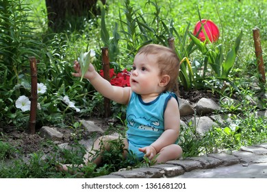 Emotional white kid gives a flower. A child sits near a flower bed