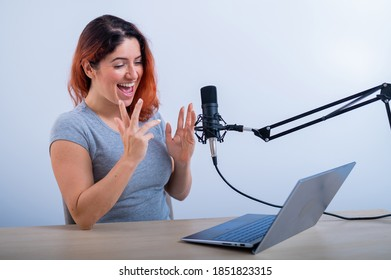 An emotional woman is broadcasting online on a laptop. Female radio presenter at the workplace
