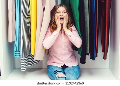 Emotional woman choosing her fashion outfit. Shopping girl thinking what to wear in front of many choices of clothes. Pretty woman sitting among clothes in wardrobe. Nothing to wear concept