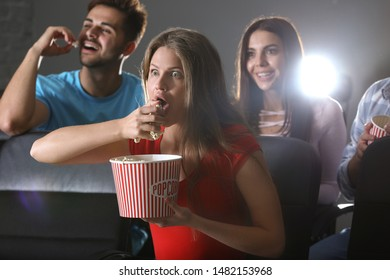 Emotional woman with popcorn watching movie in cinema