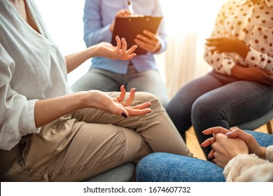 Emotional woman sharing her story during support session for addicts, close up on gesticulating hands. Close-up of therapist's hands explaining a problem to his patients