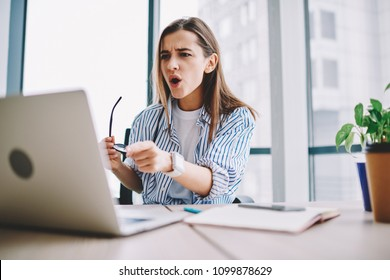Emotional woman stressed while watching video on laptop computer sitting in office interior, shocked female pointing on netbook irritated about application failure during working process at desktop