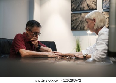 An emotional worried senior man with serious illness gets a bad diagnosis from compassionate doctor in hospital. Caucasian female health specialist showing emphaty towards patient while touching hand