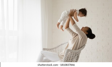 Emotional young african american mother sitting on comfortable chair, raising on straight arms laughing adorable toddler baby son or daughter, having fun playing together in light living room.