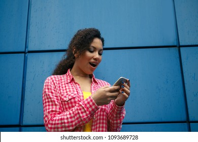 Emotional young attractive female expressing surprise checking email box and reading messages with congratulation of winning using modern smartphone connected to 4G internet in coworking office