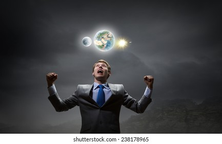Emotional young businessman looking up and screaming. Elements of this image are furnished by NASA